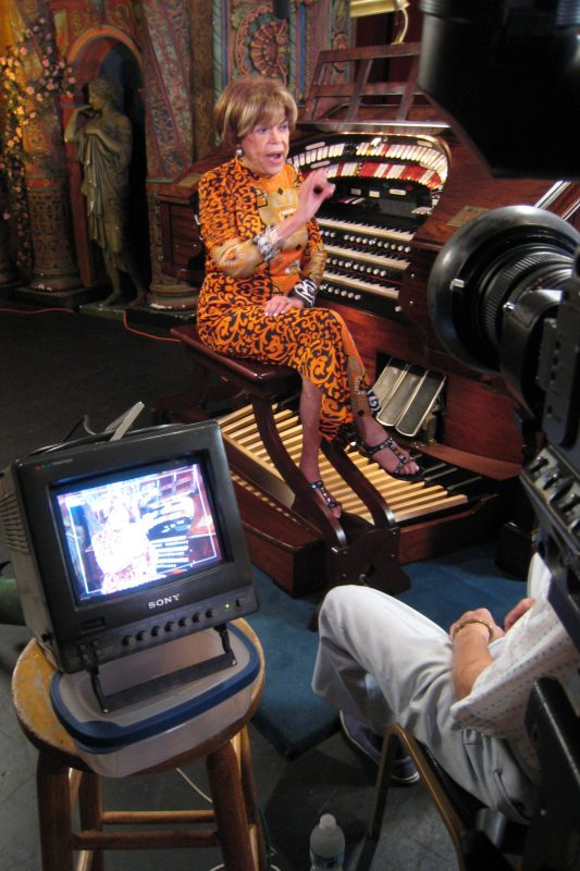 Rosa at console Wurlitzer Tampa Theatre orange dress & monitor foreground interview shoot IMG_0964